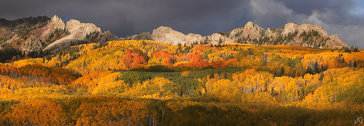 Near Kebler Pass, sunset light hits the Ruby Range, the Dyke and the autumn aspen forest below.