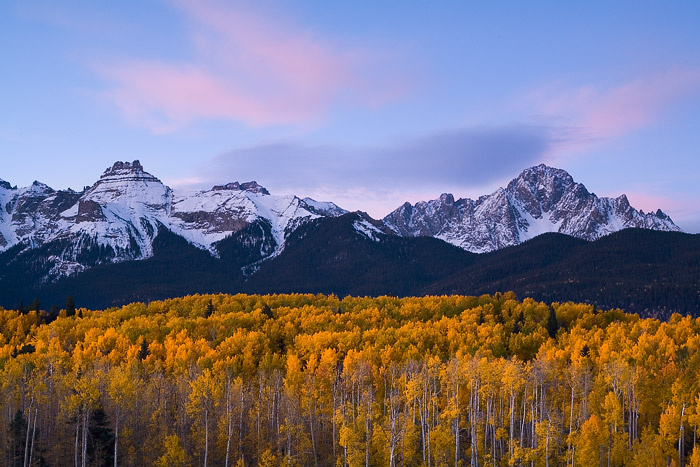 Early morning light paints the clouds above the Sneffels Range a beautiful pastel color, while the aspens below glow in the soft...