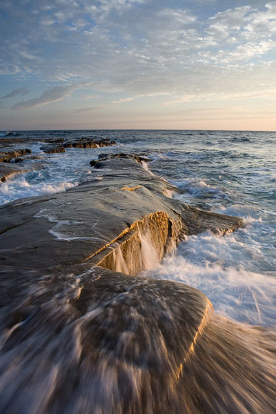 Incoming water forces its way up and onto a coastal shelf near La Jolla, California.