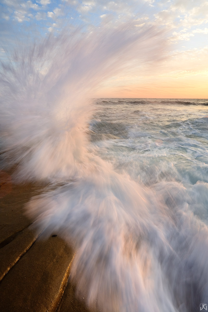 Waves crashing onto sea shelf on the coast near La Jolla, California, shimmer in the soft light of sunset.