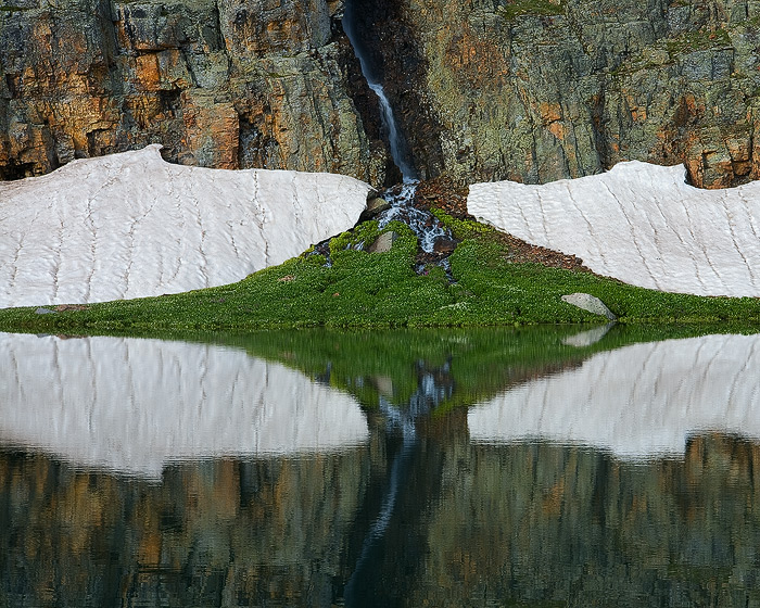 Rocks, snow and colorful streaks are reflected in Bullion King Lake.