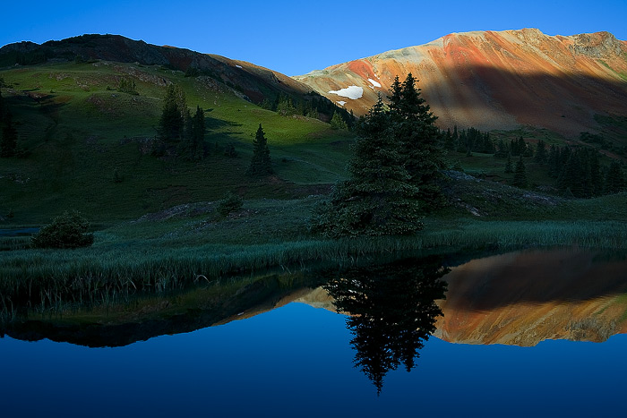 Early morning light brightens a summer green hillside and Red Mountain.