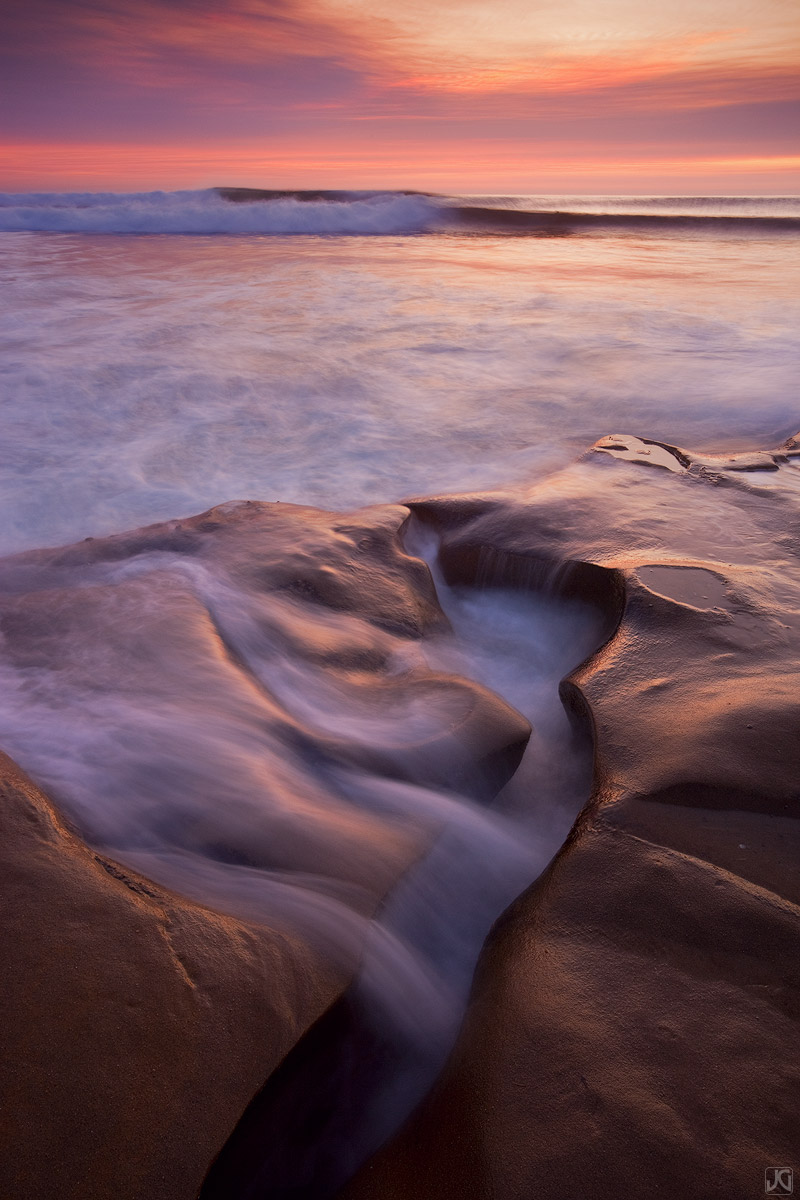Soft sunset light and the incoming tide wash over this stretch of the beach in San Diego.