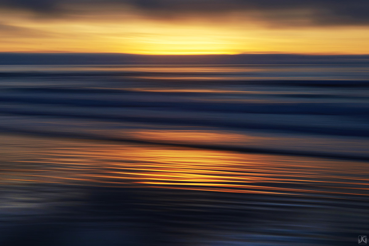 Sunset's golden glow reflects off the ripples and sand.