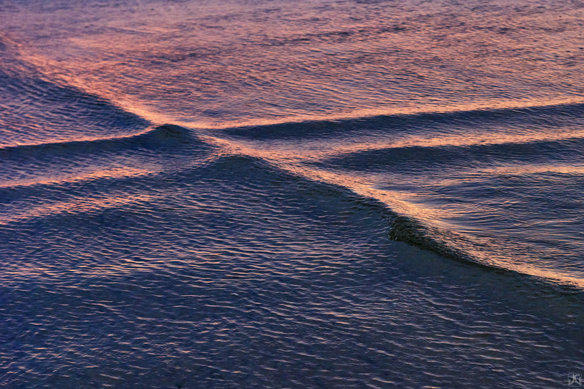 As the glow from sunset and clouds above lights up the shallow waters, the ripples and waves dance and collide with each other...