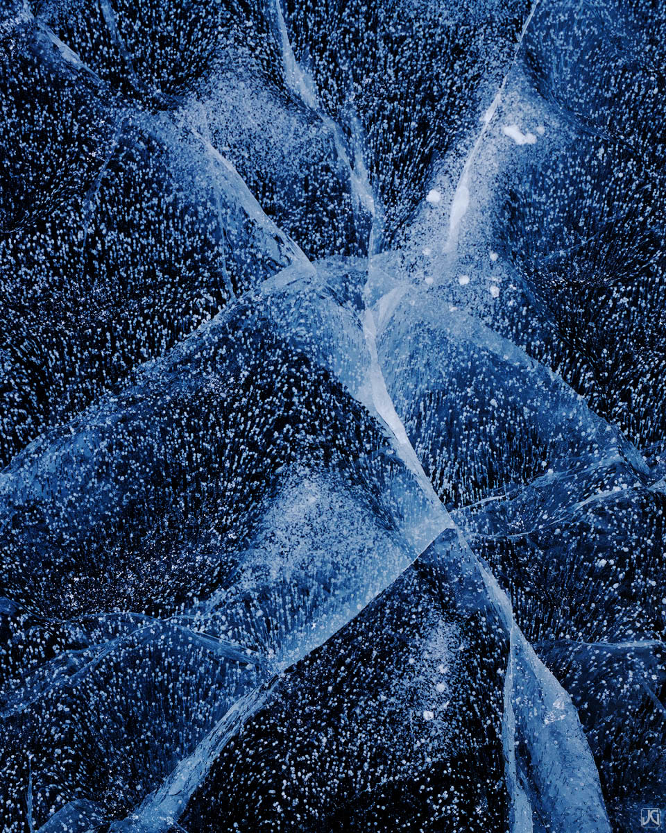 Patterns from ice cracks and bubbles on a frozen lake are akin to the clear night sky.