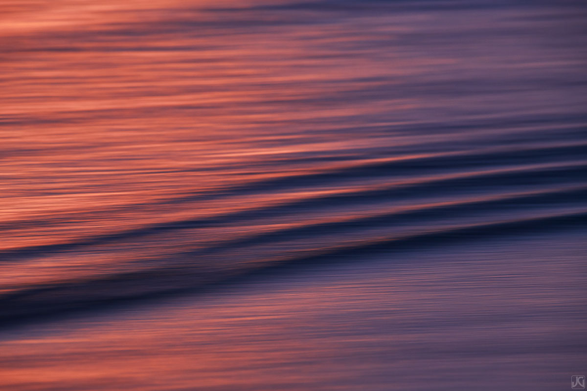 A colorful sunset bounces off the clouds above, reflecting in ripples near the coast.